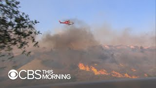 High winds accelerate two deadly wildfires in Southern California