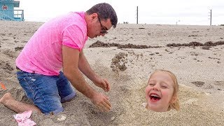 Nastya và cha giả vờ chơi trên bãi biển