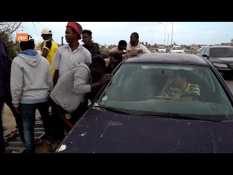 عمال أفارقة يتجمعون حول سيارة رجل ليبي. المصدر: جولي دانغلهوف / مهاجر نيوز