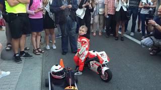 Трёхлетний ребёнок управляет мотоциклом одной рукой .