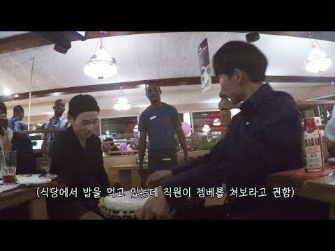 Restaurant staff in South Africa give a group of Korean guests a jembe to try. That group is a showchoir ensemble ..