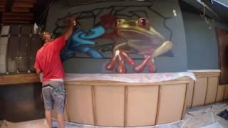Pintando un graffiti de una rana en Croak's Restaurant