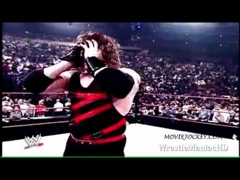 kane removes his mask and show his burning face