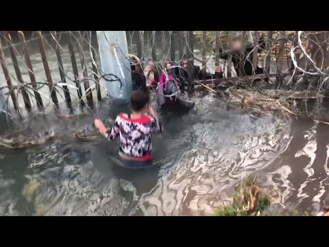 As sirens wail in the background, migrant smugglers push adults and children through a hole beneath a border wall in a video provided by US Customs and Border Protection. An advocate for the migrants says it shows their desperation. (April 2)