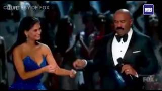 Pia Wurtzbach gives Steve Harvey a pair of eyeglasses before announcing the final result.