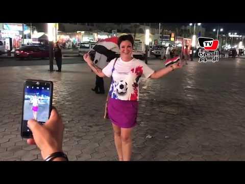سائح روسي يرتدي قميص «صلاح» : وروسية تلتقط الصور التذكارية بـ«علم مصر»