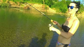 Девушка на рыбалке учится ловить рыбу