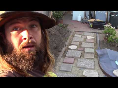 Backyard Ecological Landscape Laying Down Patio Pavers and Gravel Pathways