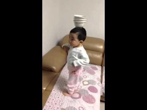 ילד קטן ומוכשר רוקד בלי להפיל קערות מהראש שלו
