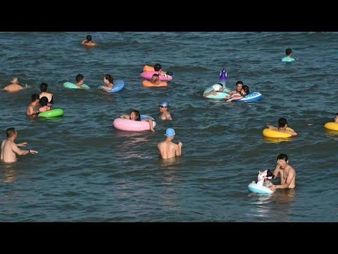 العرب اليوم - شاهد: روّاد شاطئ صيني يُزيّنون مياهه بالعوامات الملونة
