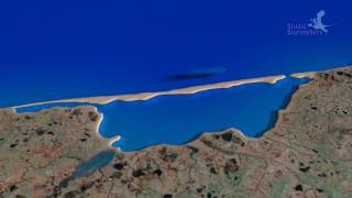 Longshore drift creating a spit and turning bay into lagoon