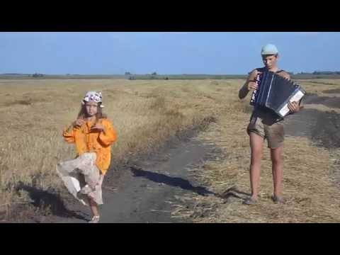 Girl dances while her brother plays the accordian in a field in Russia