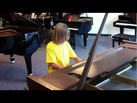 Kid covers Through The Fire and The Flames on piano with no sheet music, a faster tempo than the orignal, while headbanging.