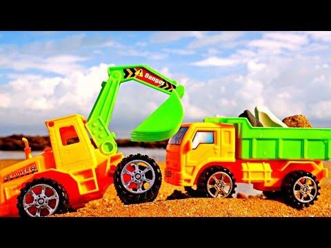 Los coches recogen piedras. Camiones de juguete en la playa.