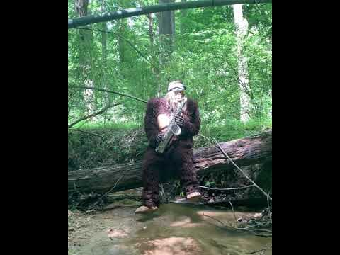 Man Dresses Up As Big Foot & Plays Saxophone In The Forest