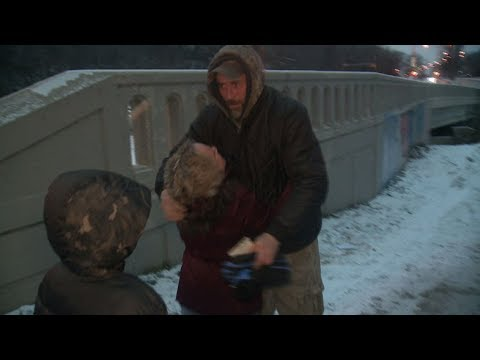 Woman lends a helping hand to homeless man in need.