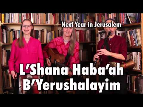 "Three musicians standing in front of two bookcases, playing Bulgarian tupan, guitar, Bulgarian flute, and darabuka on ""L'Shana Haba'ah B'Yerushalayim."" This is a still from a video of the Ensemble M'chaiya performing live."