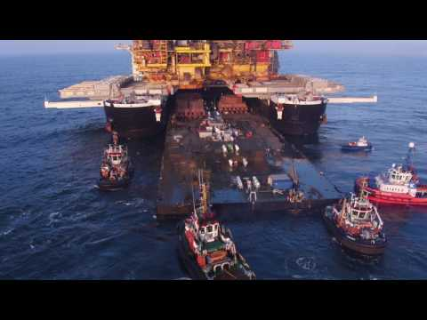 The biggest ship on Earth picking up an oil rig and delivering it to shore.