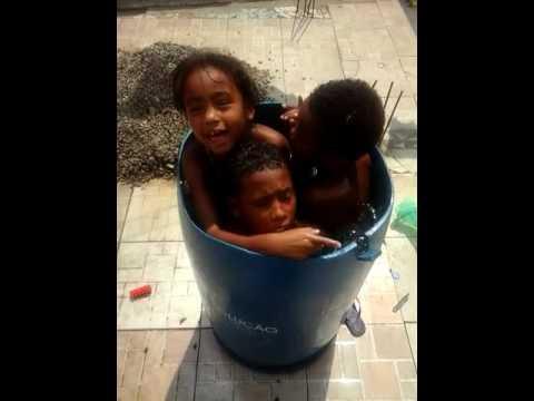 Meninos e meninas tomando um banho de bacia.