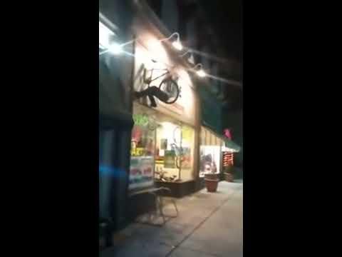 這男的神經病,喝醉後爬牆..騎上了掛在二樓牆外的單車