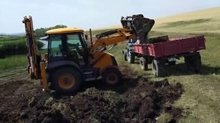 Экскаватор погрузчик JCB загружает пять тракторов мтз с  землей /Moldova