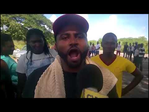 Persons from Clarendon protest the road condition.