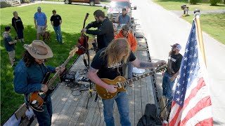 The group Nick Bosse and the Northern Roots play on a flatbed trailer as it drives through North Stonington on Sunday