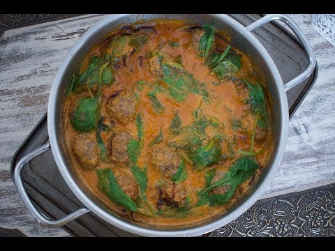 Tasty mutton meatballs with baby spinach in coconut sauce