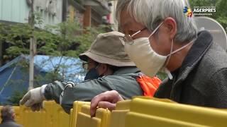 Comercianții din Wuhan își vând marfa din spatele unor bariere construite pe străzi