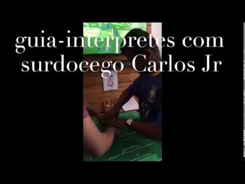 Brazilian deaf-blind soccer fan being guided to watch his team score a goal