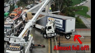 Big rig crashes and is left dangling off freeway bridge in Los Angeles!