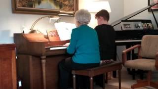 Nic playing piano with his tutor.