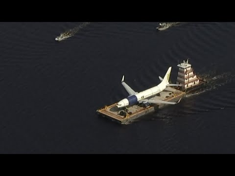 A barge and a crane are moving the Miami Air International plane that ran off a runway and into a river at a Florida military base on Saturday. (May 8)
