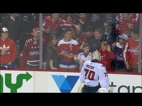 8a120399e21 Holtby not amused as adult fan takes puck away from younger Capitals fan