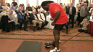 Mark Henry attempts to lift the legendary Thomas Inch Dumbbell with one hand (WWE Network)