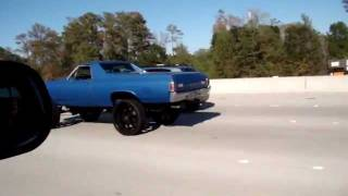 Car with big ass wheels going down the freeway