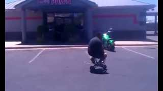 Big Dude On Tiny Bike in Front of Family Pawn