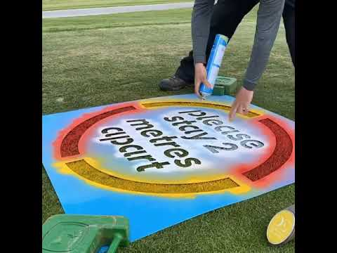 Multi coloured social distancing stencil being applied to a green at Darwin Escapes