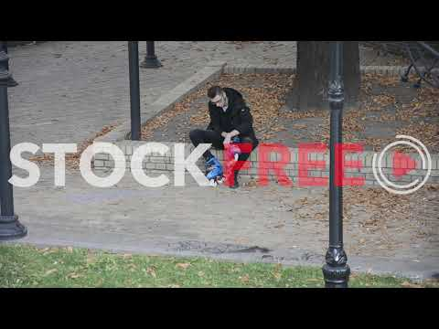 Man putting on rollers in the park   Free Stock Video Footage