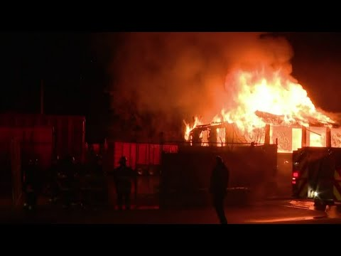 Firefighters work to keep flames away from Hamtramck business