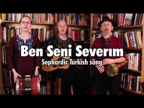 "Three musicians standing in front of two bookcases, playing Bulgarian tupan, guitar, and darabuka on ""Ben Seni Severım,"", a Sephardic song with lyrics in Turkish and Ladino. This is a still from a video of the Ensemble M'chaiya performing live."