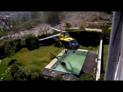 Helicopter needs water to put out a fire so expertly takes it from a nearby pool without landing.