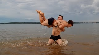 WRESTLING IN WATER: two muscle brothers flexing and wrestling. And then have fun cliff jumps