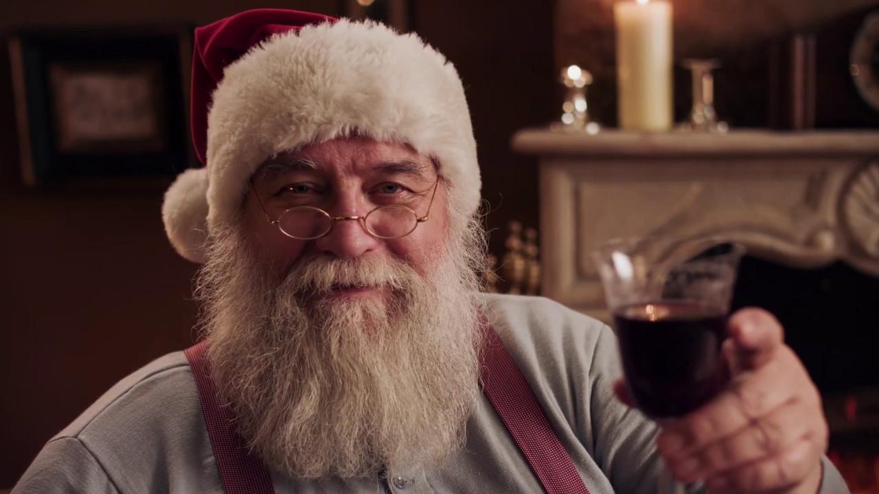 Video-Thumbnail von Videogrußbotschaft: Weihnachtsmann lächelt in Kamera und hält ein Rotweinglas zuprostend ins Bild