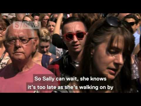 Crowds in Manchester sing 'Don't Look Back in Anger' after minute's silence