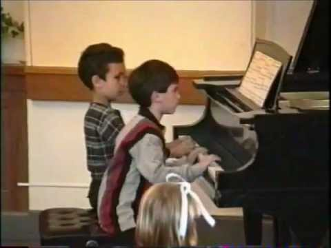Two piano students perform duet together.