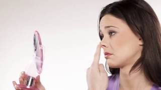 Woman looking in mirror touching her nose