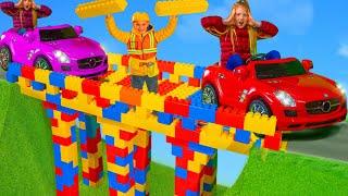 Kinder bauen eine Brücke mit Bagger, Feuerwehrautos, Polizeiautos und Spielzeugfahrzeugen