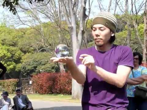 Giocoliere di strada con sfera di cristallo - contact juggling