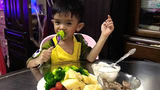Small kid eat vegetables salad